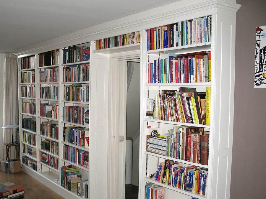 Witte open boekenkast boven de deur