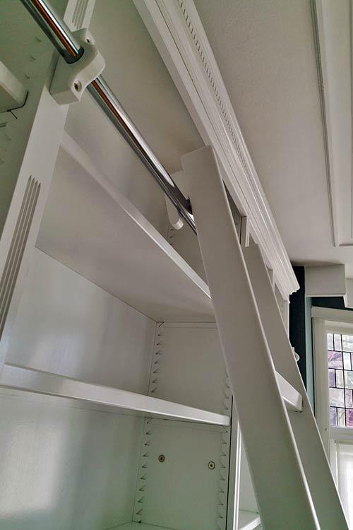 witte boekenkast met ladder en zig-zag plank verstellers